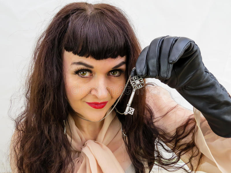 Mujer que lleva a cabo una llave con la mano con guantes fotografía de archivo
