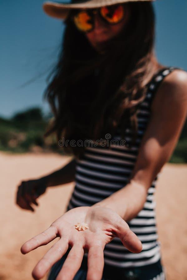 Mujer que lleva a cabo una pequeña cáscara en la mano en la línea de la costa foto de archivo libre de regalías