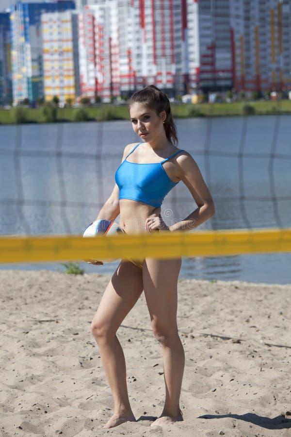 Mujer que lleva a cabo voleibol en la playa fotos de archivo