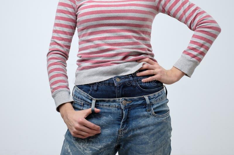 Mujer que lleva dos pantalones de los vaqueros Moda extraña e impar Ella es muy descuidada imagenes de archivo