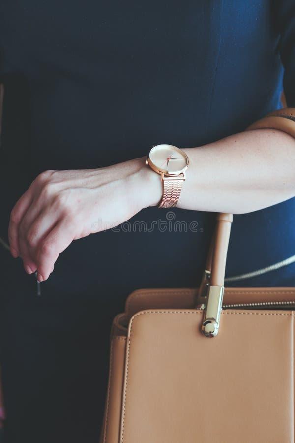 Mujer que lleva el reloj rosado del oro y el vestido azul que llevan a cabo el leathe fotografía de archivo libre de regalías