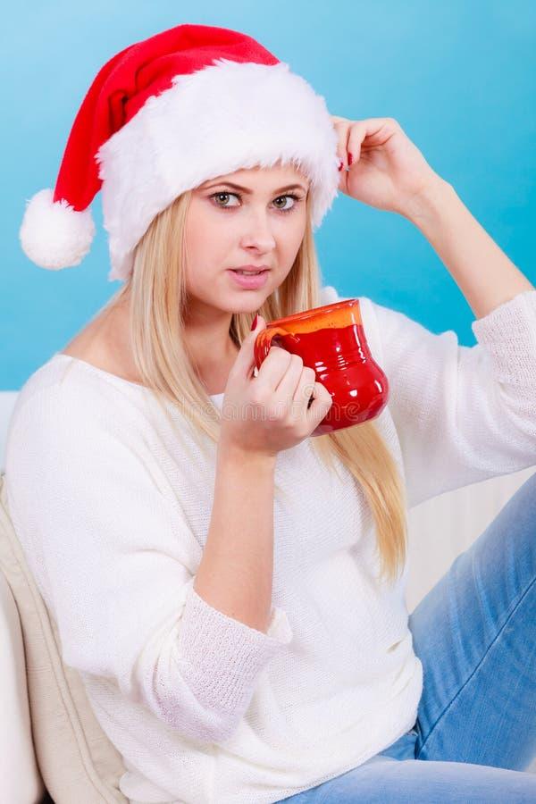 Mujer que lleva el sombrero de Santa Claus que bebe la bebida caliente imagen de archivo libre de regalías