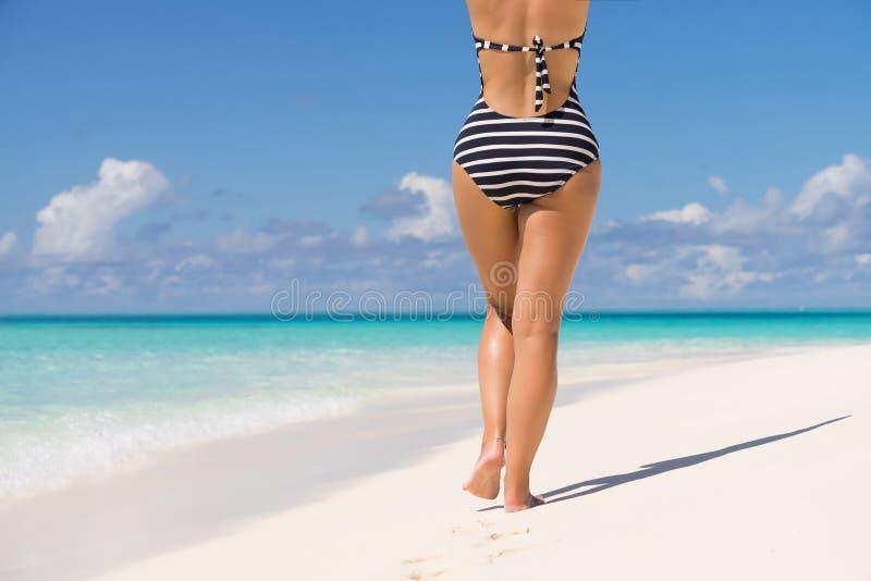 Mujer que lleva el sombrero rayado retro del bikini y de la playa, gozando de amazi foto de archivo libre de regalías