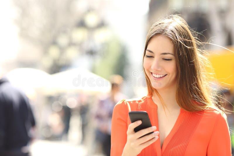 Mujer que lleva la camisa anaranjada que manda un SMS en el teléfono elegante imagen de archivo