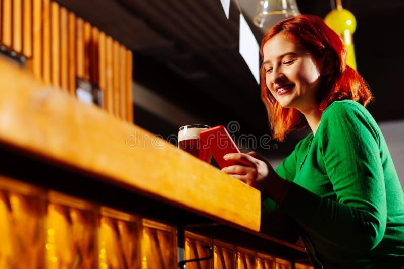 Mujer que lleva la camisa verde que se sienta en el soporte de la barra y que usa el teléfono imagen de archivo