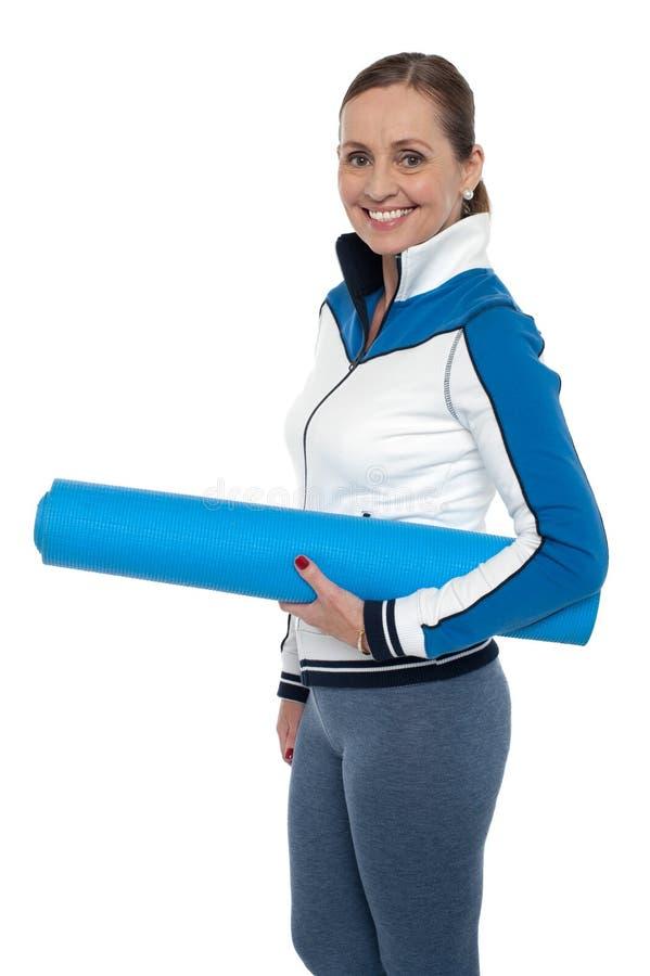 Mujer que lleva la estera azul de la yoga foto de archivo