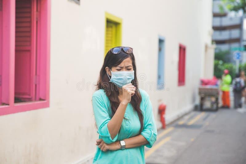 Mujer que lleva la mascarilla médica en ciudad imágenes de archivo libres de regalías