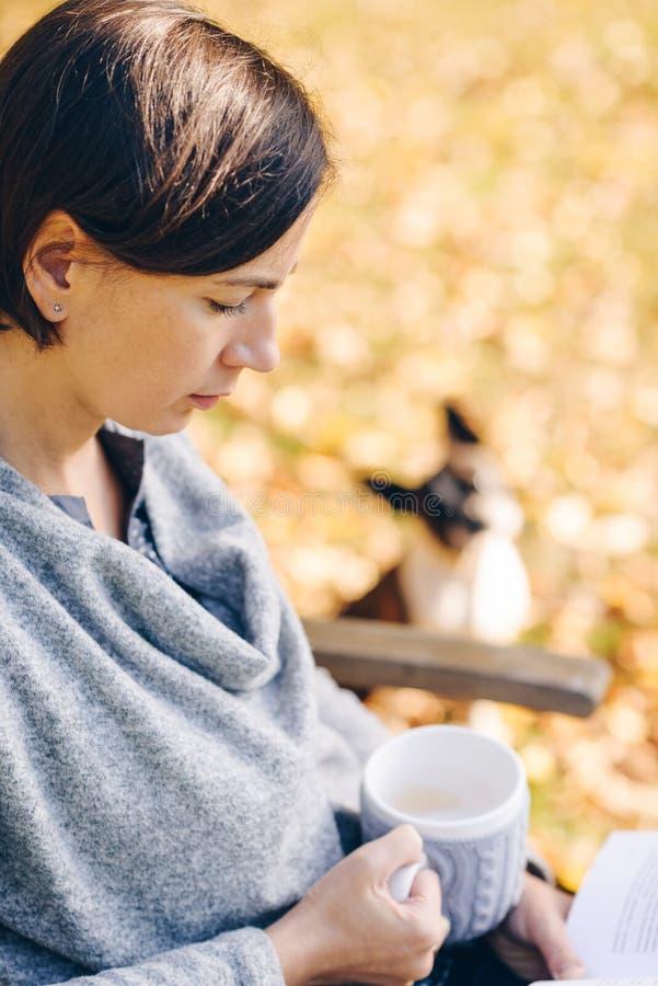 Mujer que lleva la ropa de punto caliente que bebe una taza de té o de cof caliente imágenes de archivo libres de regalías