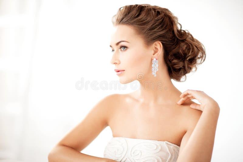 Mujer que lleva los pendientes brillantes del diamante foto de archivo