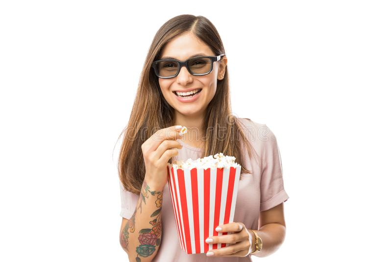 Mujer que lleva los vidrios 3D mientras que goza de película y de las palomitas fotos de archivo