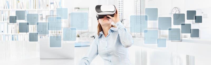 Mujer que lleva los vidrios de la realidad virtual en oficina, con el icono vacío fotos de archivo libres de regalías