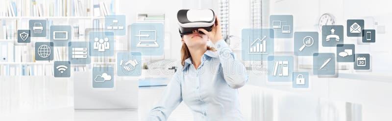 Mujer que lleva los vidrios de la realidad virtual en oficina, con los iconos, web imagen de archivo libre de regalías