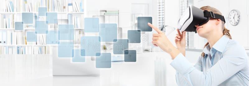 Mujer que lleva los vidrios de la realidad virtual en la oficina, mano que señala t foto de archivo libre de regalías