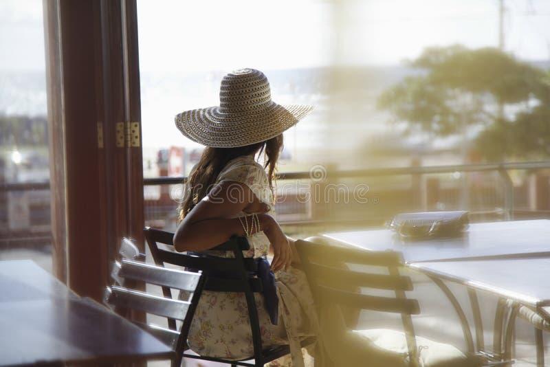 Mujer que lleva Sunhat en el café imagen de archivo libre de regalías