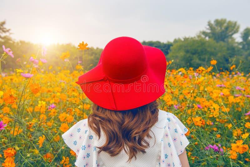 Mujer que lleva un sombrero rojo en un campo de flores foto de archivo