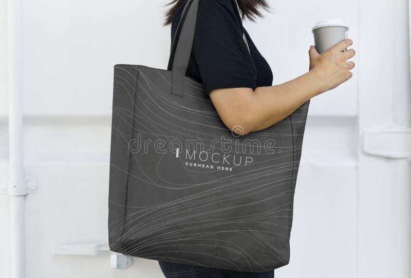 Mujer que lleva una maqueta negra del bolso que hace compras imagen de archivo libre de regalías