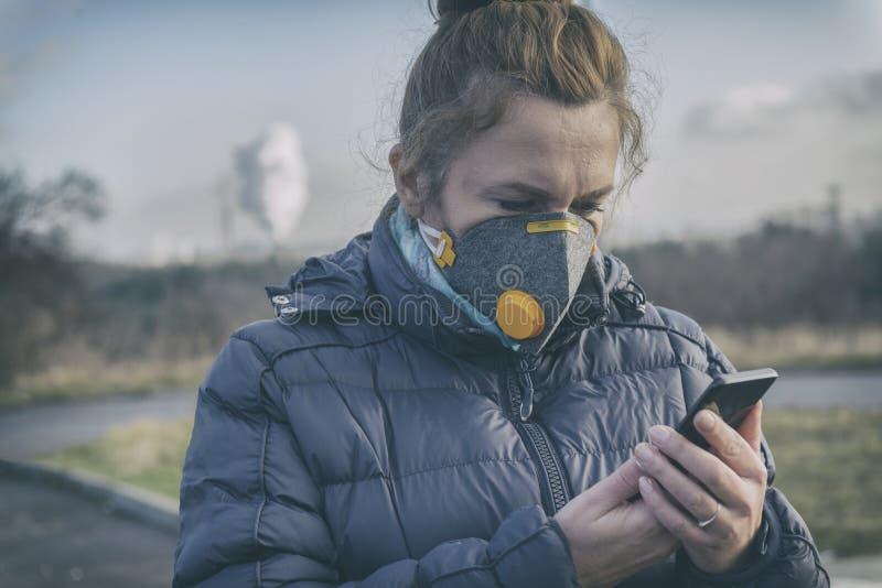 Mujer que lleva una mascarilla contra la niebla real y que comprueba la contaminación atmosférica actual con el app elegante del  foto de archivo