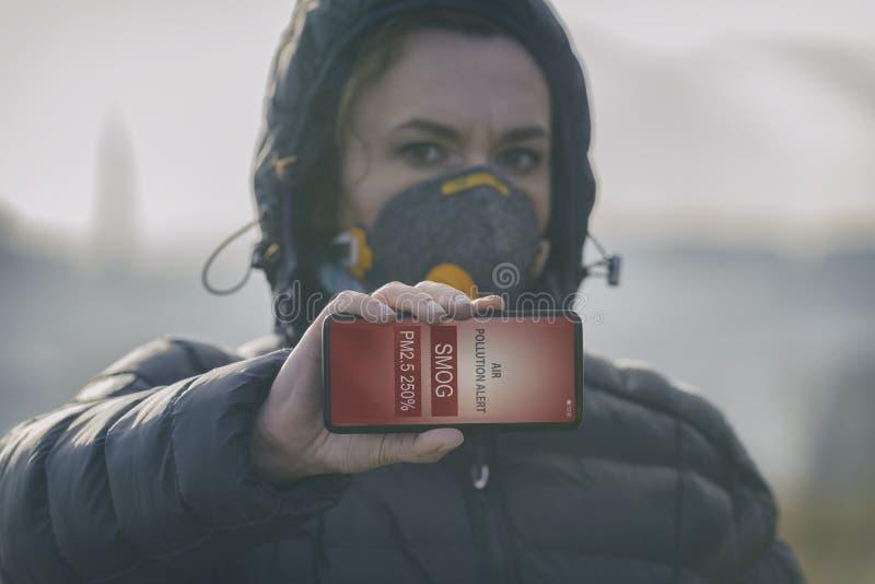 Mujer que lleva una mascarilla contra la niebla real y que comprueba la contaminación atmosférica actual con el app elegante del  imagen de archivo