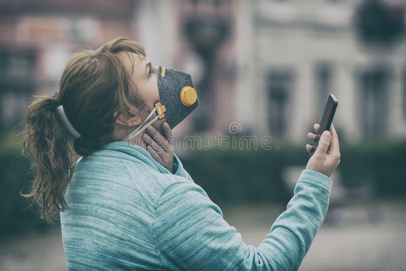 Mujer que lleva una mascarilla contra la niebla real y que comprueba la contaminaci?n atmosf?rica actual con el app elegante del t fotografía de archivo