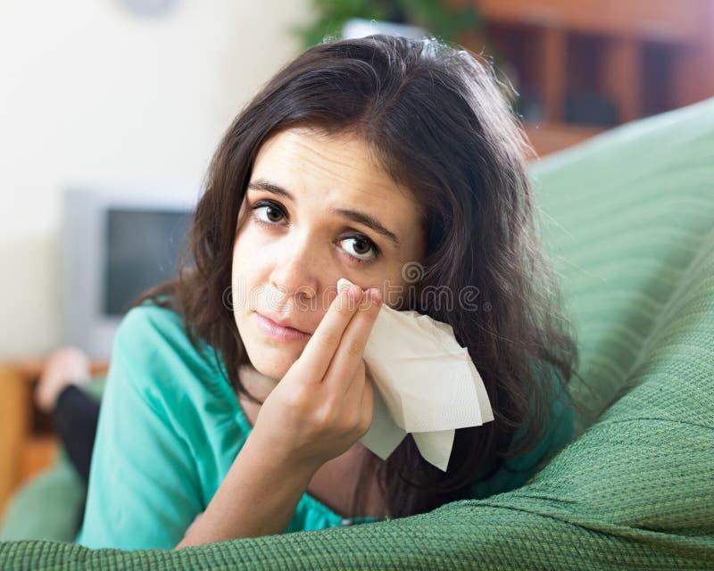 Mujer que llora en el sofá en casa fotos de archivo