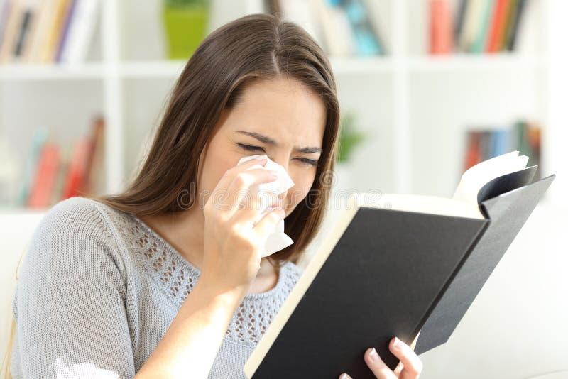 Mujer que llora mientras que está leyendo un libro de papel en casa fotografía de archivo