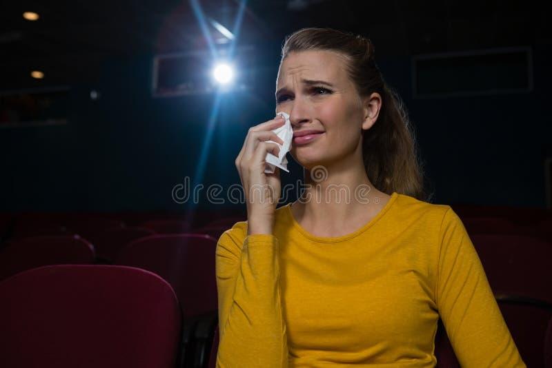 Mujer que llora mientras que mira película imagen de archivo libre de regalías