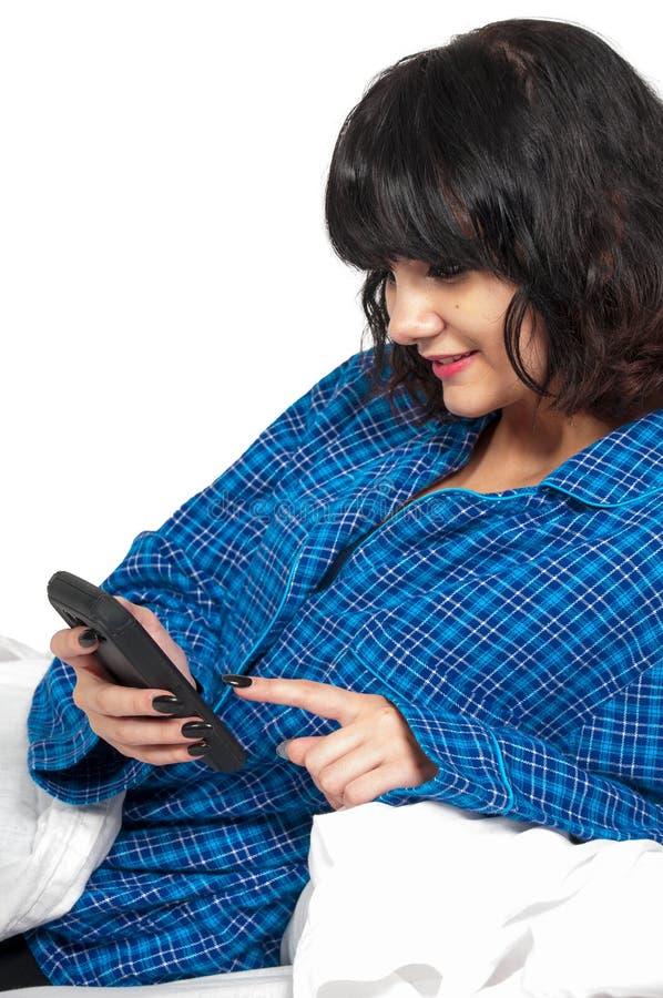 Mujer que manda un SMS en cama imagen de archivo libre de regalías