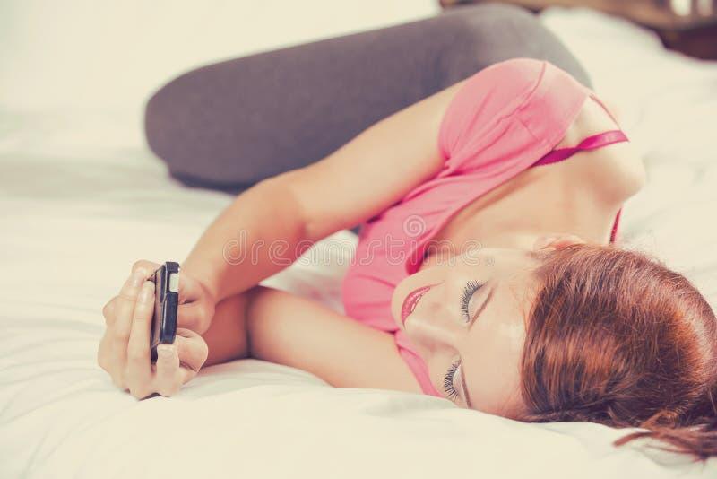Mujer que manda un SMS en el mensaje de la lectura del teléfono móvil que pone en cama fotos de archivo