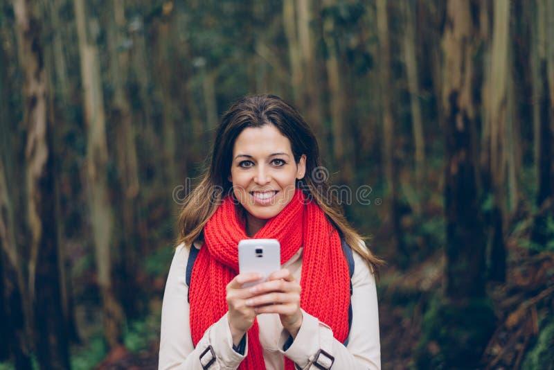 Mujer que manda un SMS en smartphone durante un viaje al bosque imagen de archivo libre de regalías