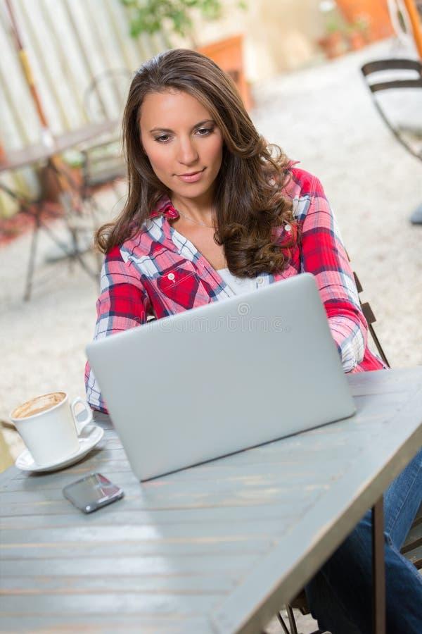 Mujer que mecanografía del ordenador portátil fotografía de archivo
