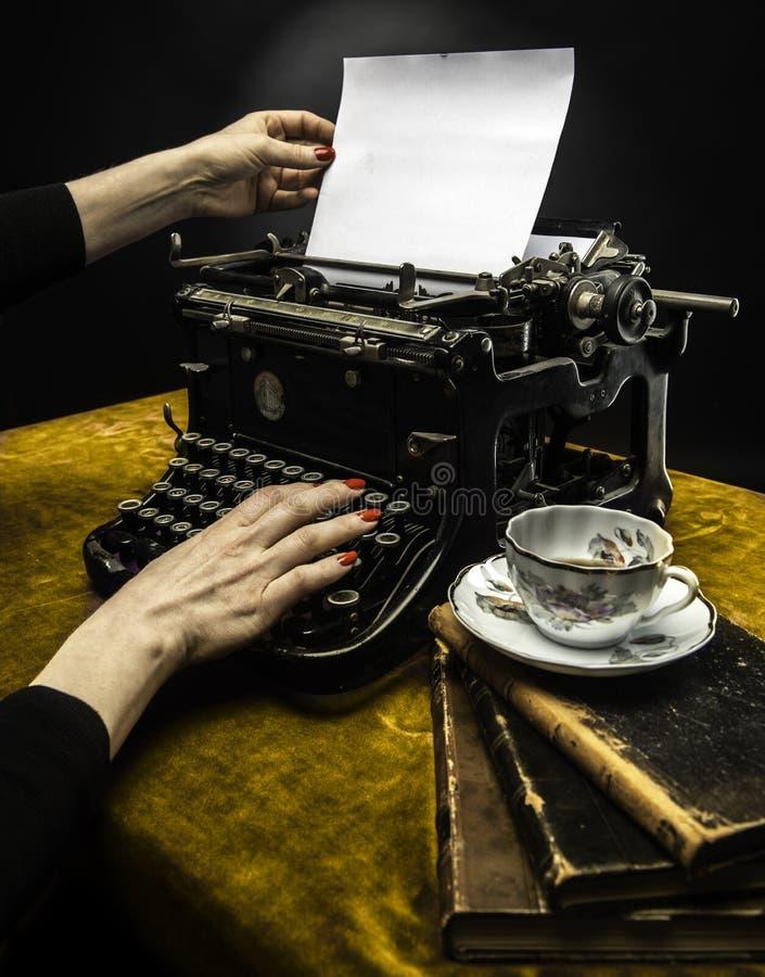 Mujer que mecanografía en una máquina de escribir vieja fotos de archivo libres de regalías