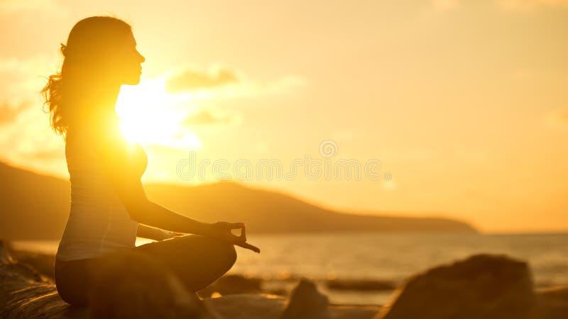 Mujer que medita en actitud del loto en la playa en la puesta del sol foto de archivo