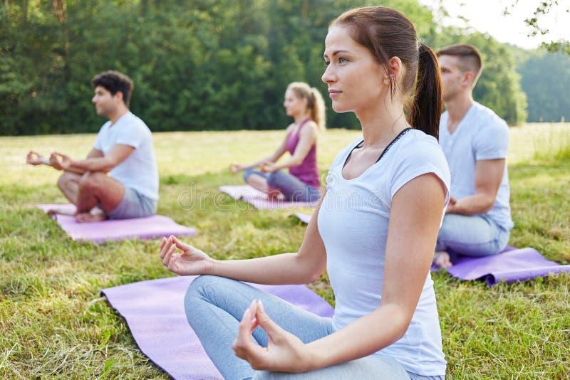 Mujer que medita en clase de la yoga foto de archivo libre de regalías