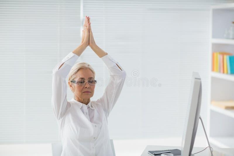 Mujer que medita en el escritorio imagen de archivo