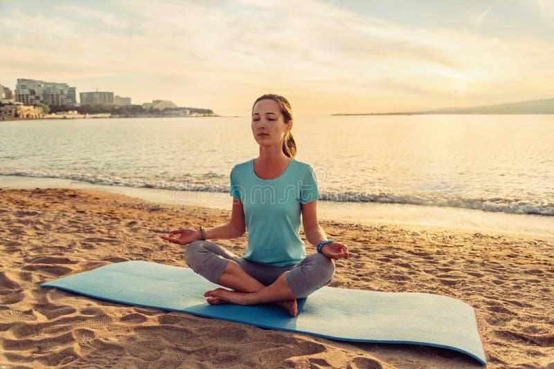 Mujer que medita en la actitud del loto en la playa imagen de archivo