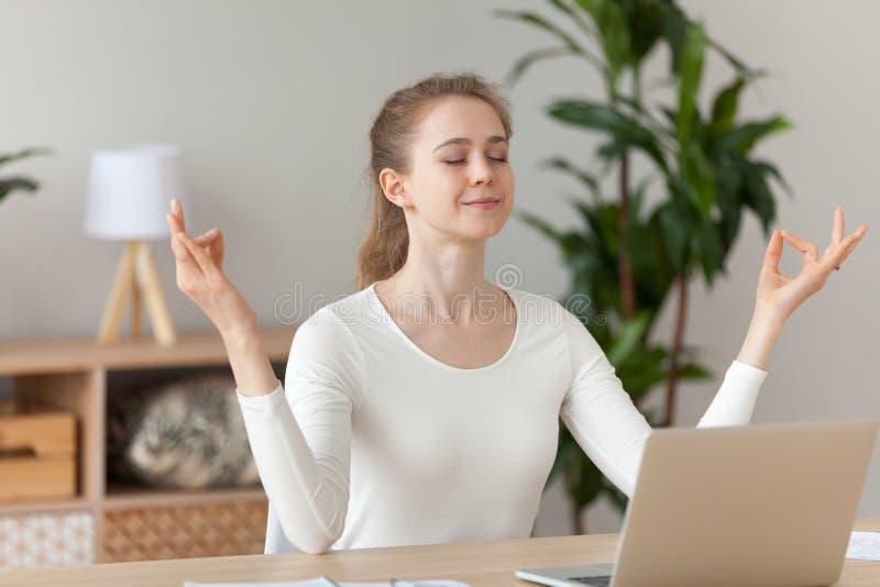 Mujer que medita haciendo la yoga que se sienta en el lugar de trabajo fotografía de archivo
