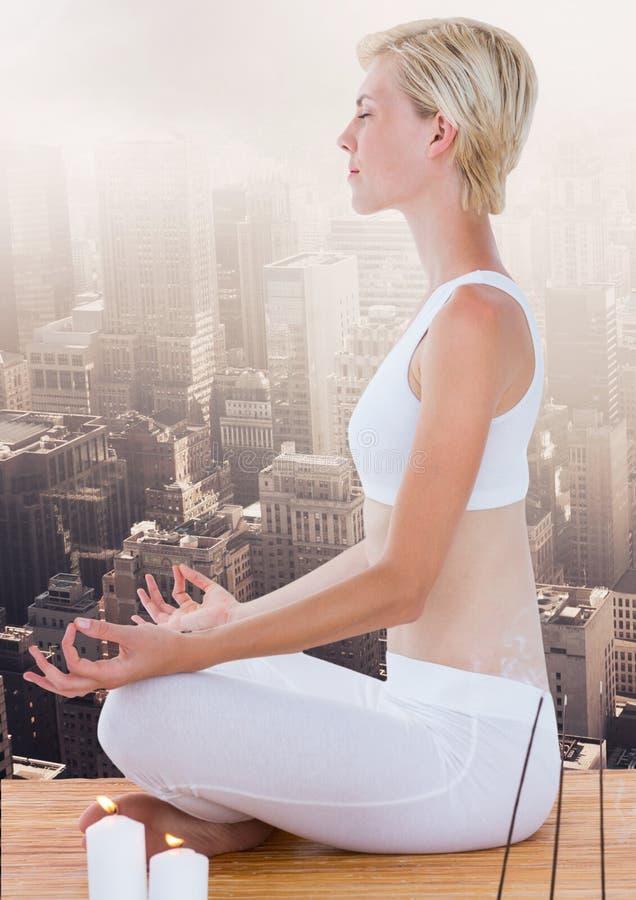 Mujer que medita la ciudad excesiva pacífica foto de archivo