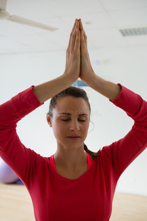 Mujer que medita mientras que hace actitud del árbol en estudio de la yoga foto de archivo