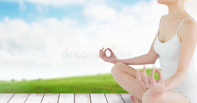 Mujer que medita por el campo y el cielo verdes fotografía de archivo libre de regalías