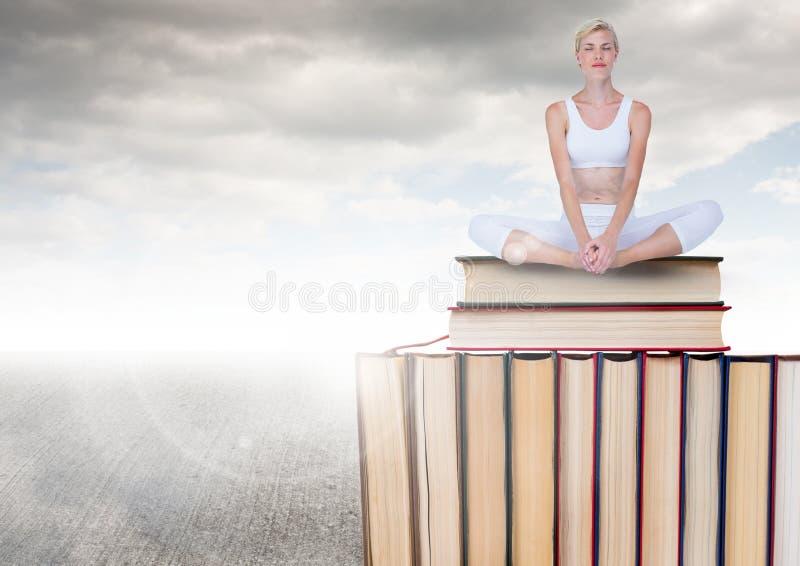 Mujer que medita sentarse en los libros apilados por el cielo nublado gris fotos de archivo libres de regalías
