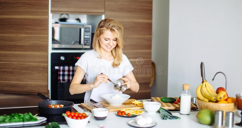 Mujer que mezcla los ingredientes deliciosos de la ensalada del superfood con las cucharas de madera en cocina fotografía de archivo libre de regalías
