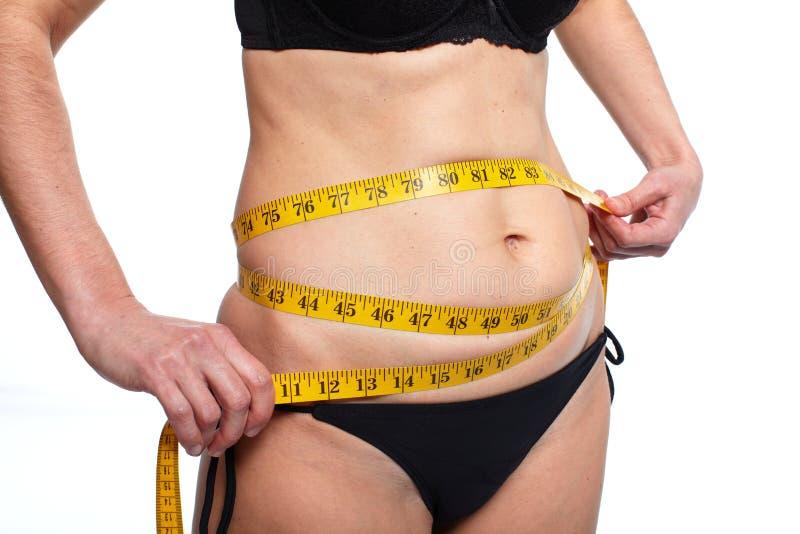 Mujer que mide el abdomen gordo imagen de archivo