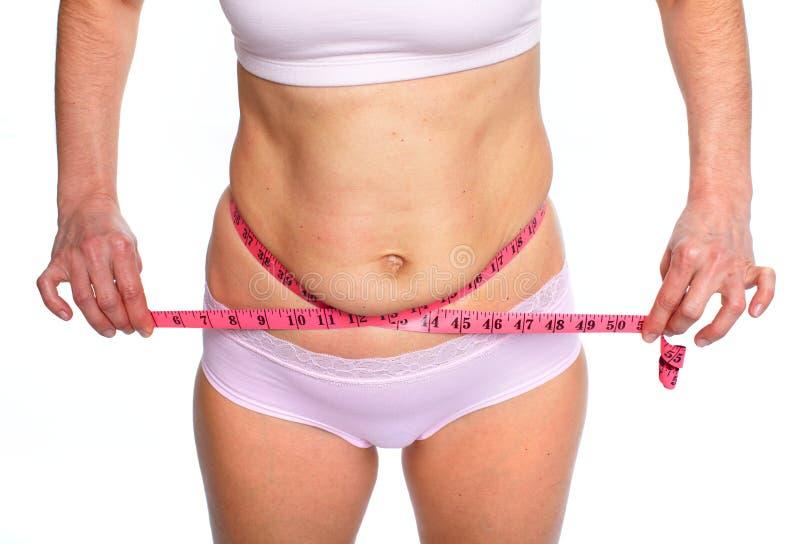 Mujer que mide el abdomen gordo foto de archivo libre de regalías