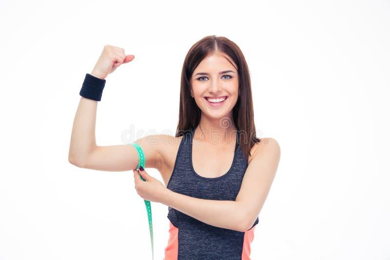 Mujer que mide su bíceps con la cinta de la medida imagen de archivo