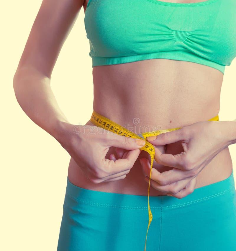 Mujer que mide su cintura imagen de archivo