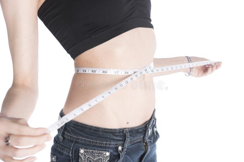 Mujer que mide su cintura usando la cinta foto de archivo libre de regalías