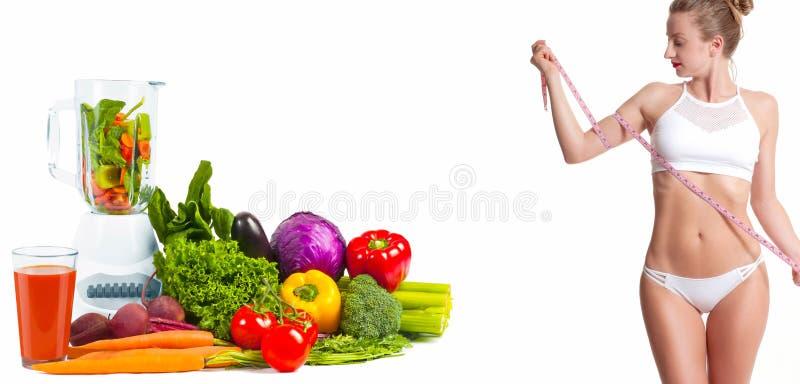 Mujer que mide su cuerpo con una cinta de la medida Concepto de la dieta, verduras frescas fotografía de archivo libre de regalías