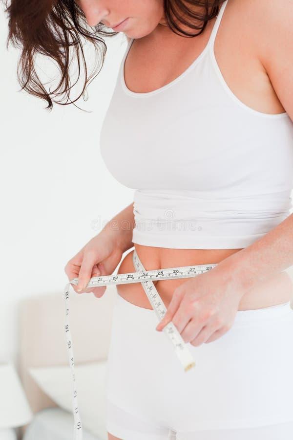 Mujer que mide su vientre con una cinta métrica fotografía de archivo libre de regalías