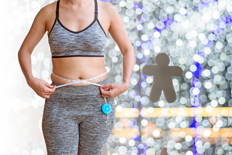 mujer que mide su vientre gordo aislado en fondo ligero del bokeh fotografía de archivo libre de regalías