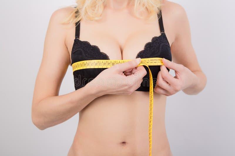 Mujer que mide sus pechos imagen de archivo